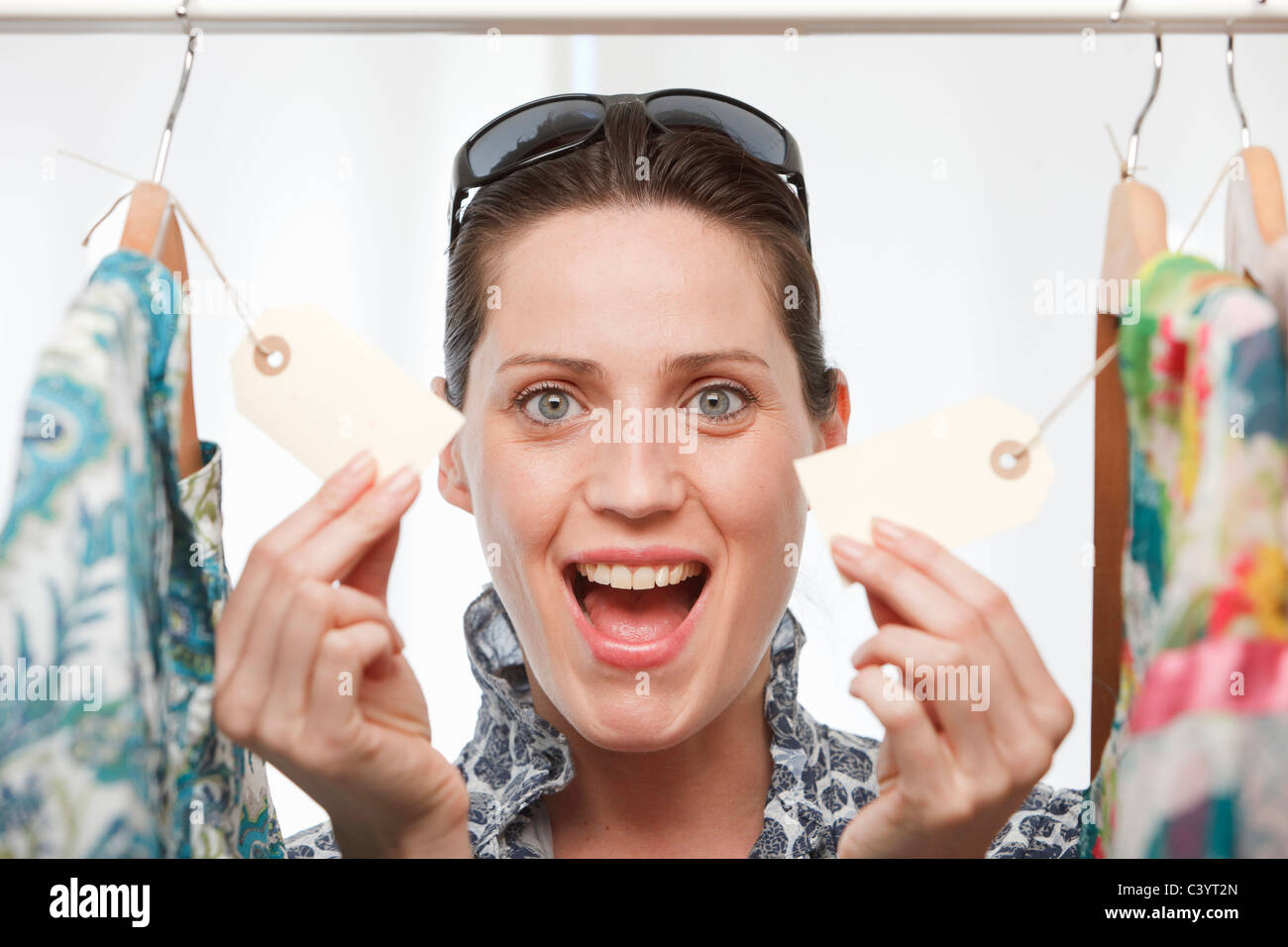woman smiling holding price tags - Stock Image