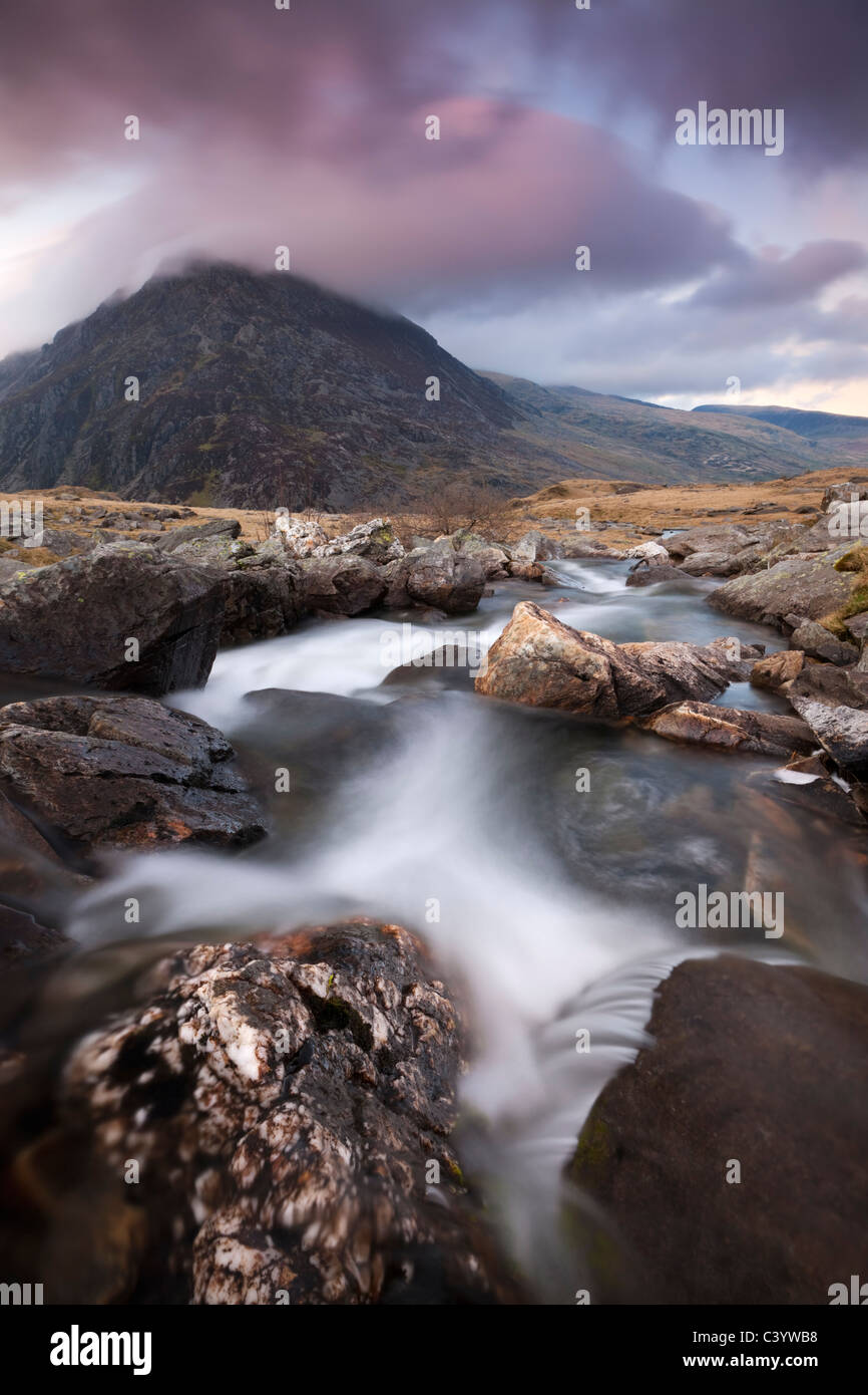 Rocky river in Cwm Idwal leading to Pen yr Ole Wen Mountain at sunset, Snowdonia National Park, Conwy, North Wales - Stock Image