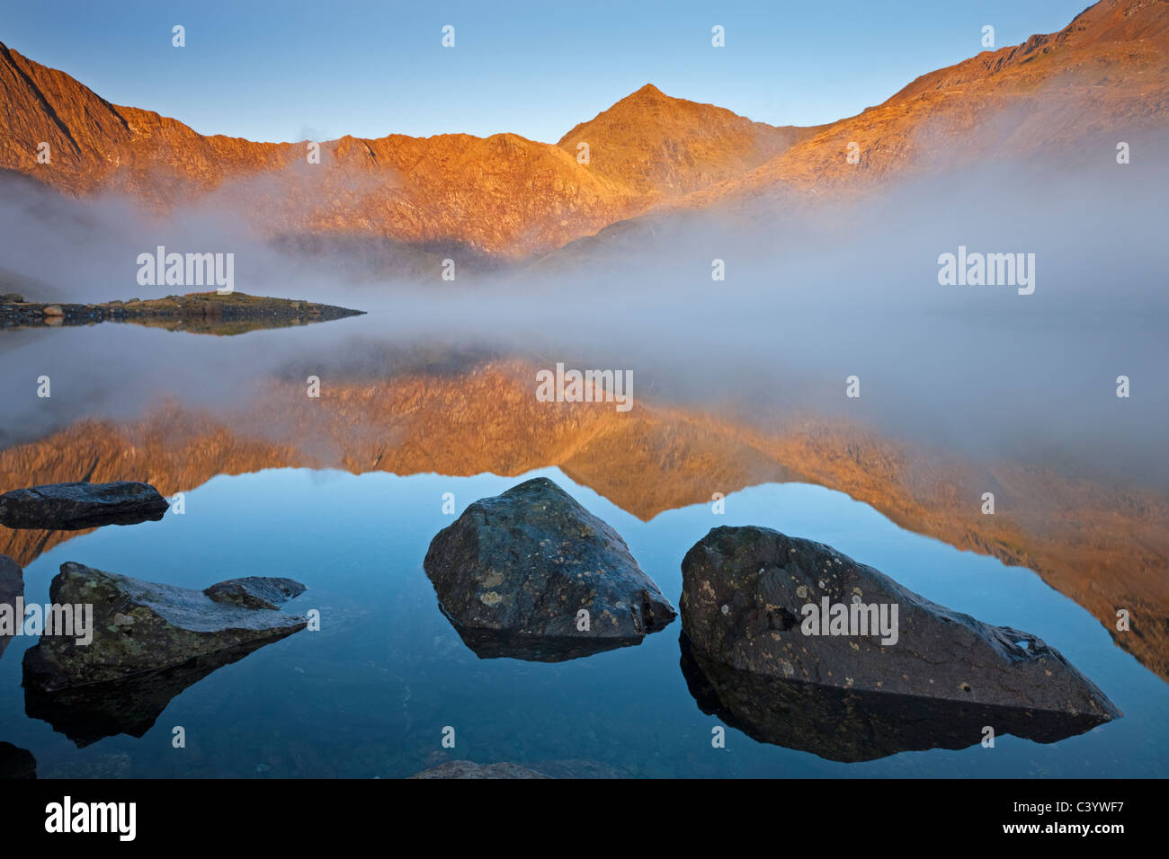 Early morning sunlight illuminates Snowdon from the shores of a misty Llyn Llydaw, Snowdonia National Park, Gwynedd, - Stock Image