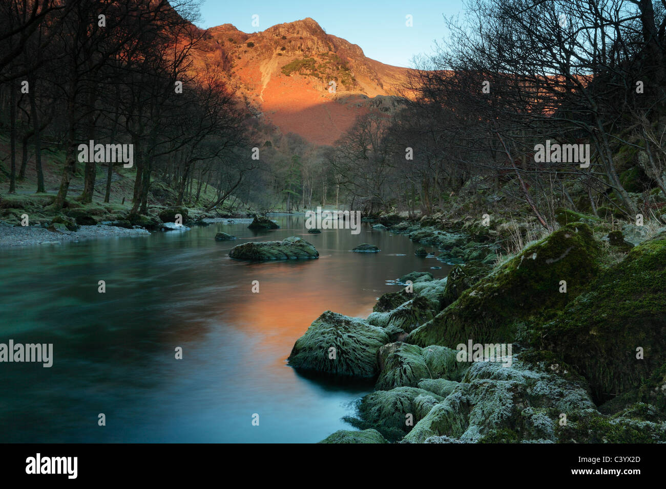 Alpenglow on High Crags is reflected in the River Derwent as seen near Rosthwaite in the Lake District of England - Stock Image
