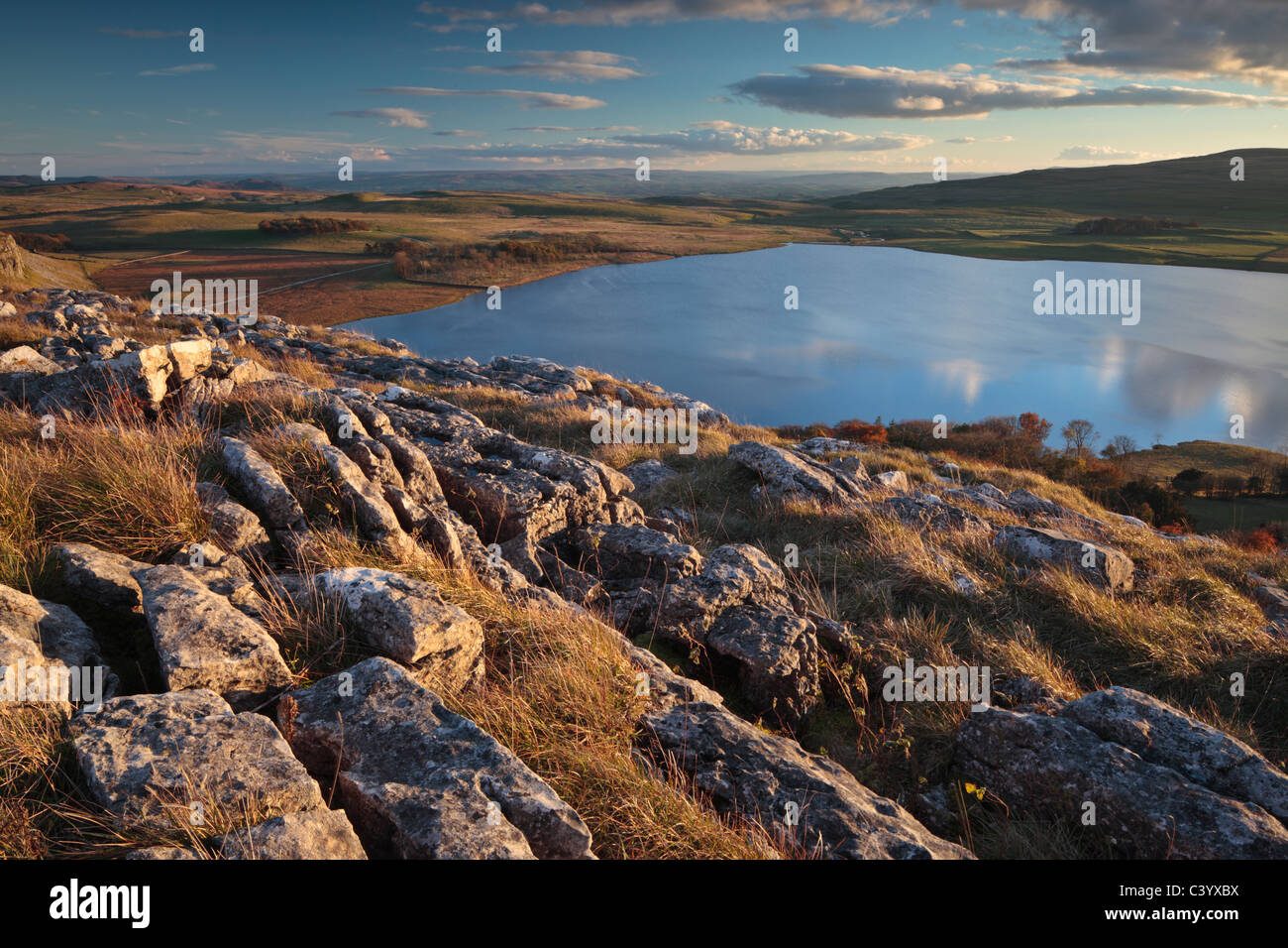 Sky and clouds reflect in the still waters of Malham Tarn in the Yorkshire Dales of England - Stock Image
