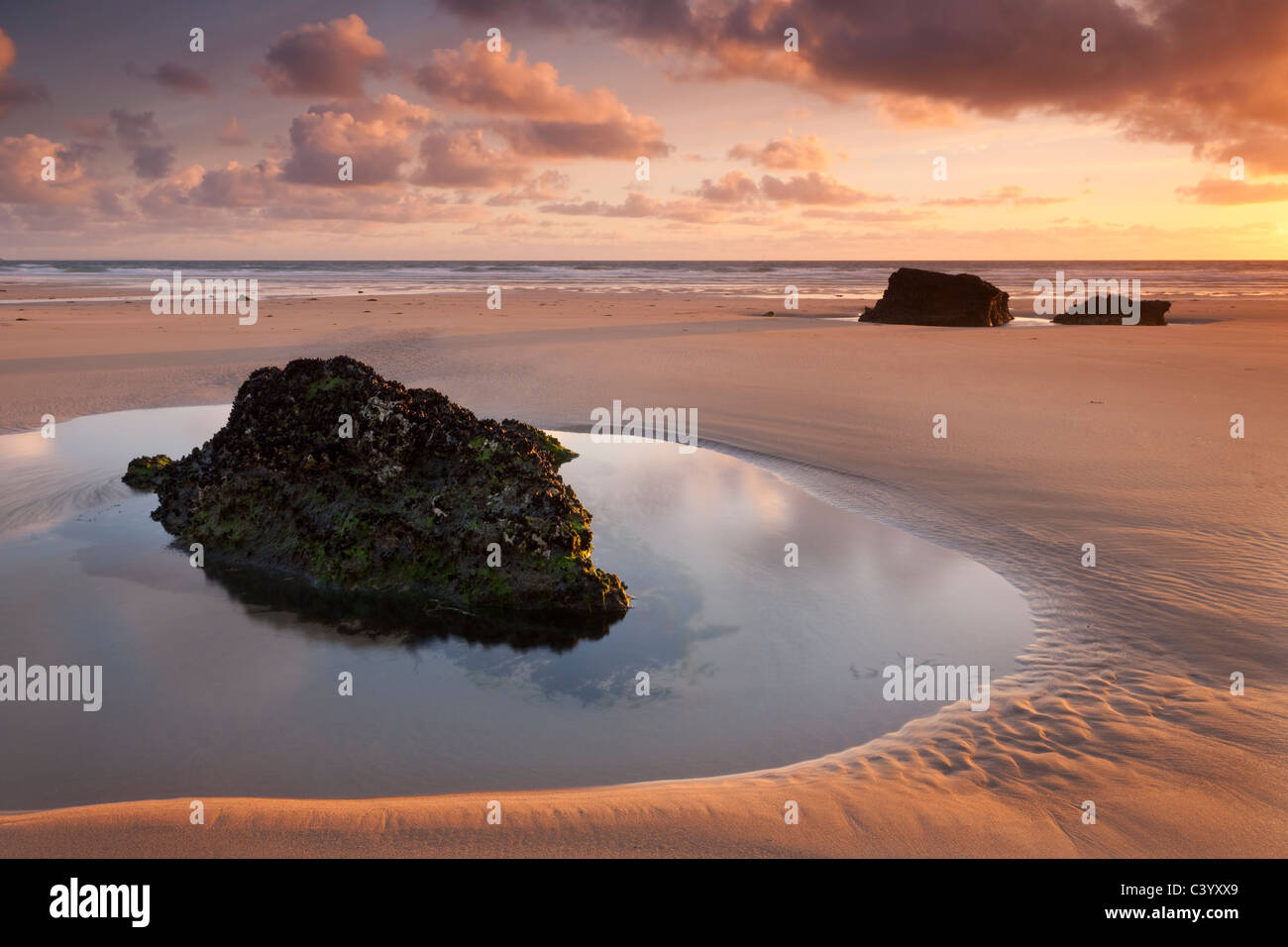 Rockpools on a deserted sandy bech at sunset, Bedruthan Steps, Cornwall, England. Spring (May) 2011. - Stock Image