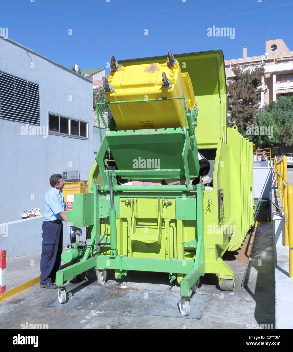 Operator tipping waste from trash bin into rubbish compactor at Clinica Hospital, Malaga, Malaga Province, Spain. - Stock Image
