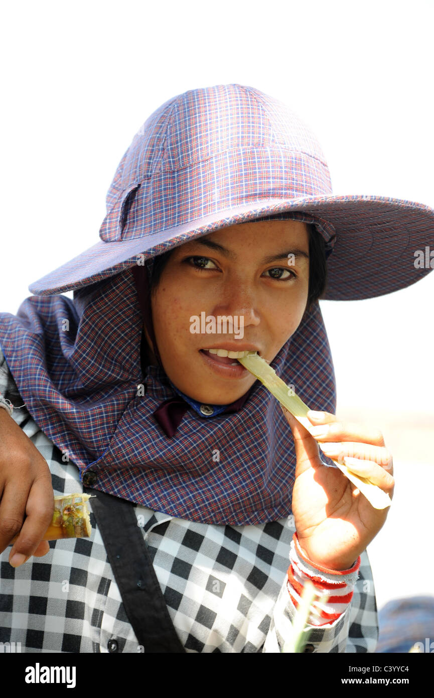 Cambodian girl chewing on a stick of bamboo in the Crab Market in Kep, Cambodia. - Stock Image