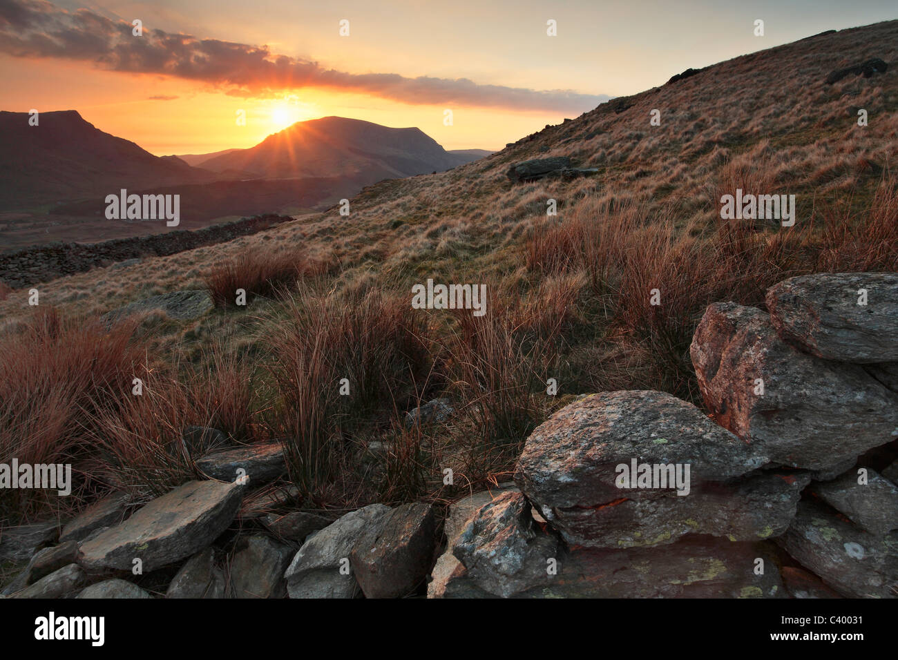 Sun sets behind Craig Cwm Silyn as seen from the Snowdon Ranger path near Rhyd Ddu in Gwynedd, Wales - Stock Image