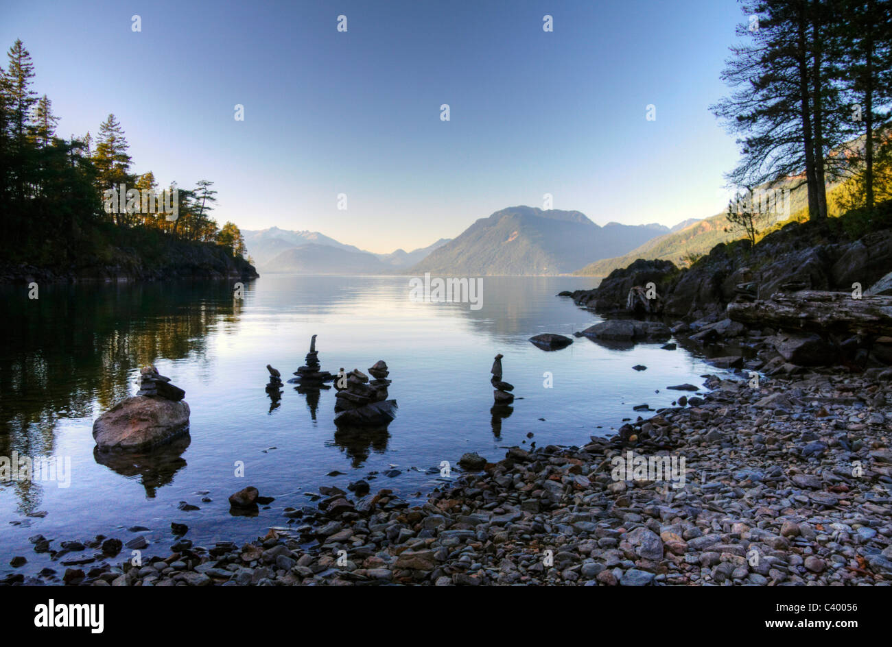 Creatively stacked stones mirrored on Harrison Lake, near Harrison Hot Springs, BC - Stock Image