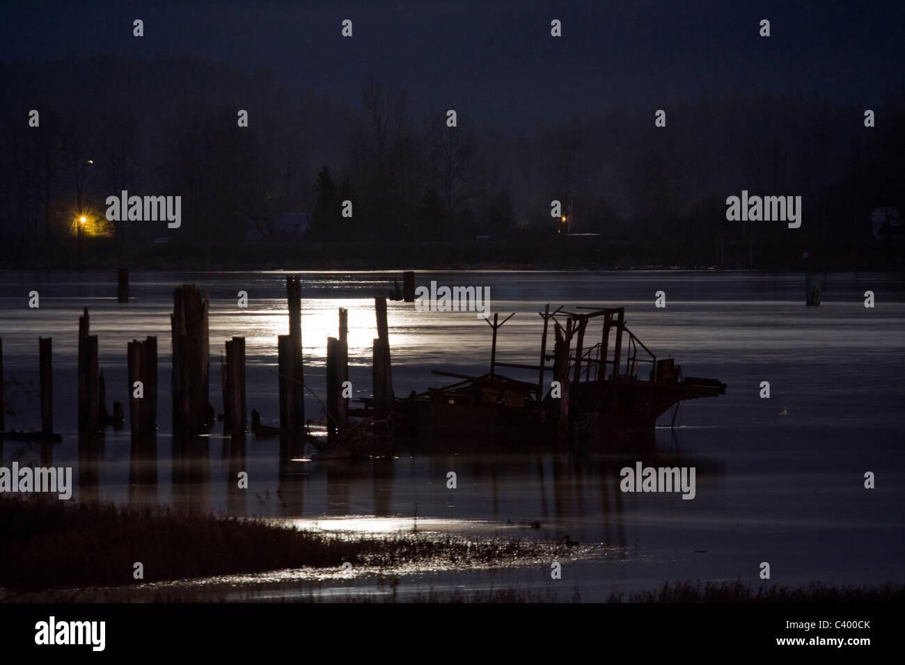 Full moon illuminates wreckage in the Pitt River, Port Coquitlam, BC, Canada - Stock Image