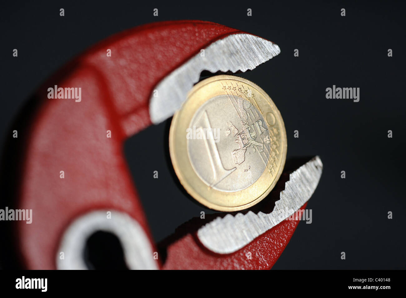 1 Euro coin in an adjustable wrench - Stock Image