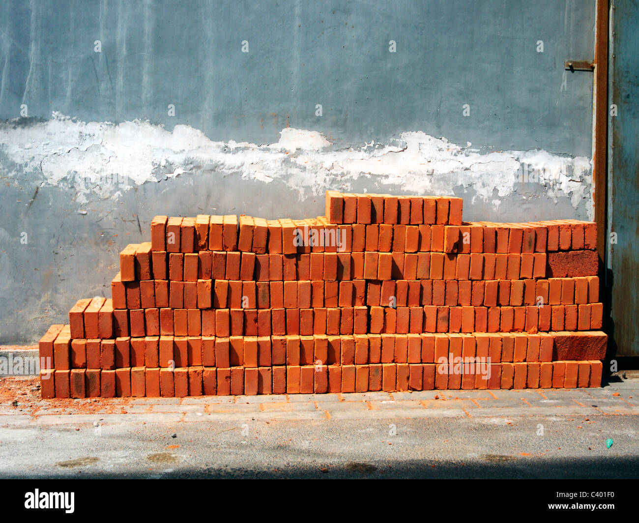 Bricks lined up against a wall in a Chinese Hutong - Stock Image