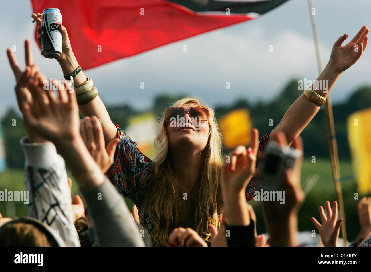 Girl on shoulders cheering at Glastonbury Festival in the sun. - Stock Image