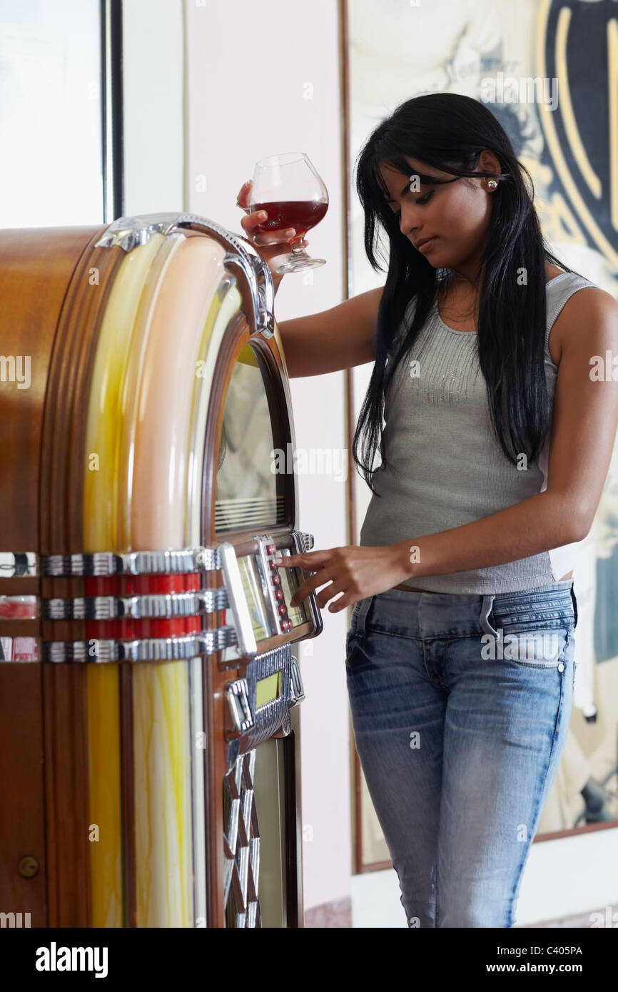 woman choosing song on jukebox, holding glass of rum - Stock Image