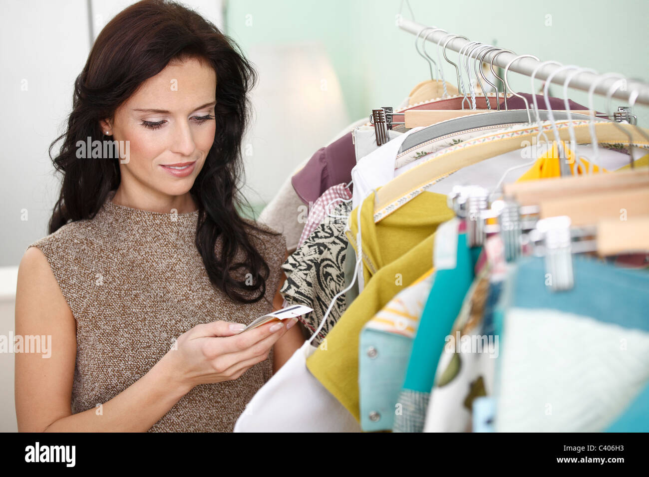 woman checking price tag - Stock Image