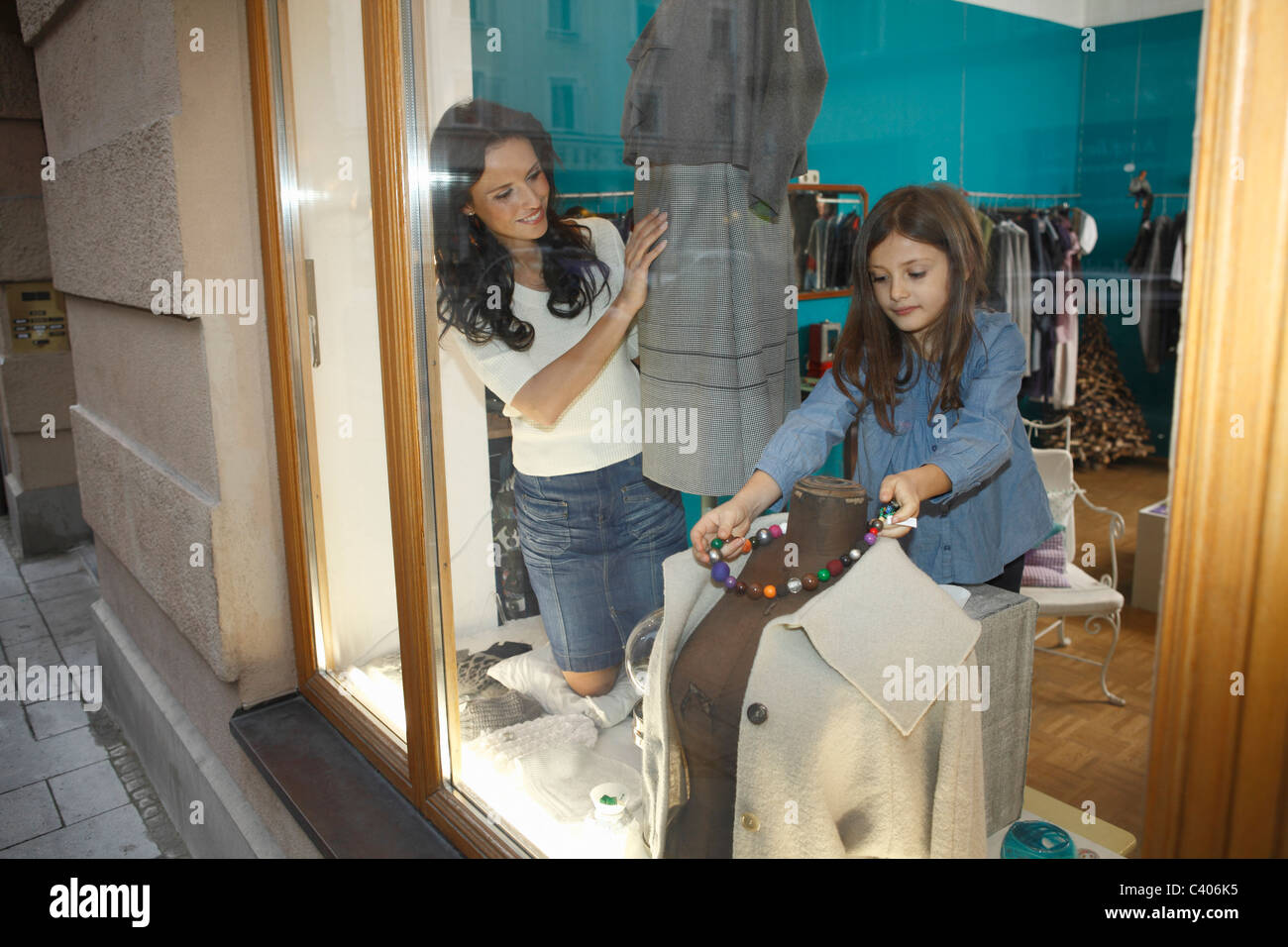 woman and girl dressing shop mannequin - Stock Image