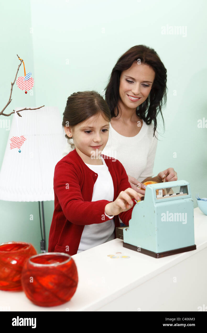 woman helping girl work shop till - Stock Image