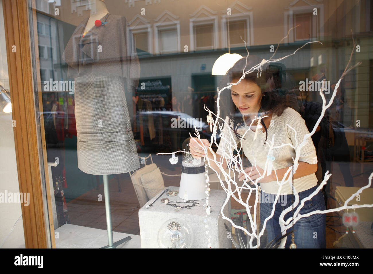 woman in shop window behind tree - Stock Image