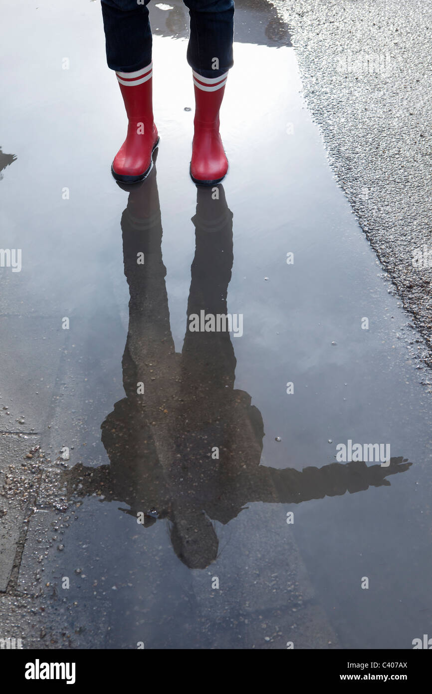 Reflection of a woman in a puddle - Stock Image