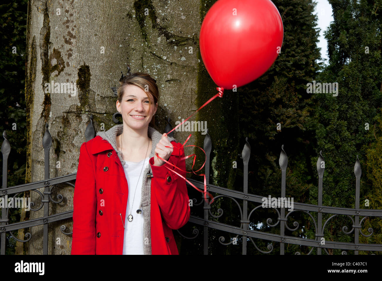 Young woman holding a red baloon - Stock Image