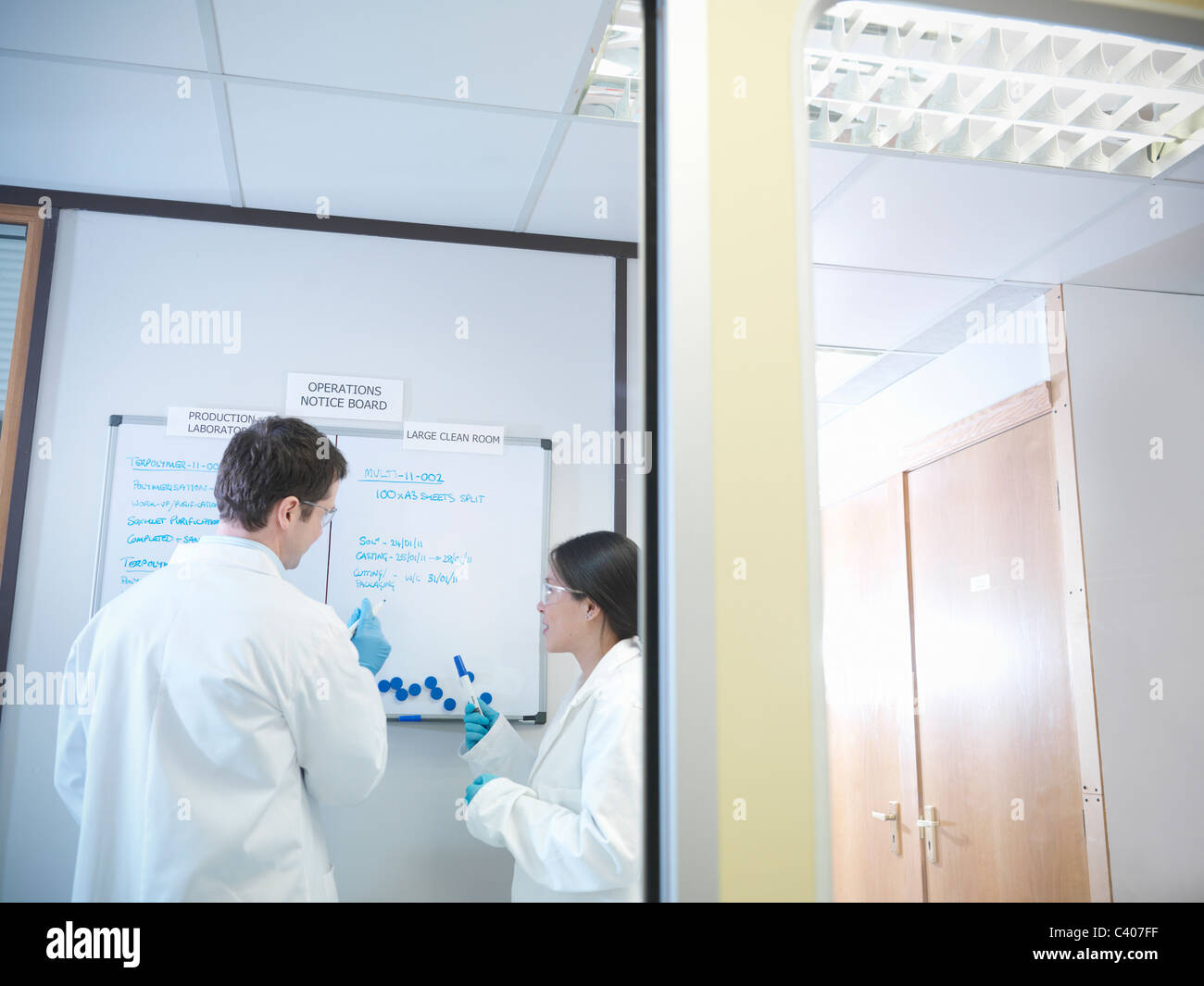 Scientists look at noticeboard - Stock Image