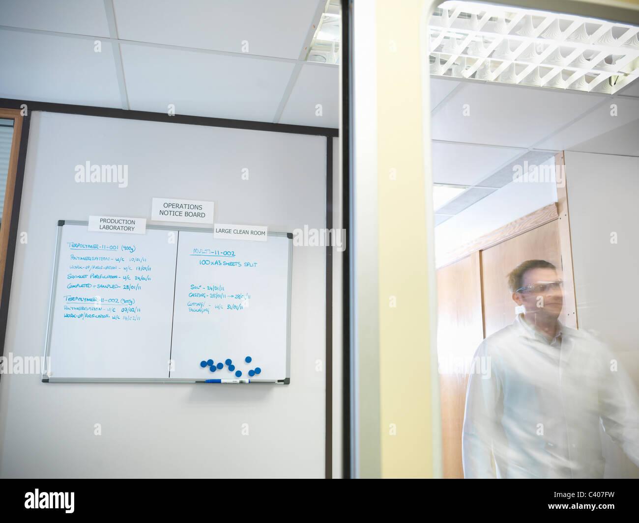 Scientist next to noticeboard - Stock Image