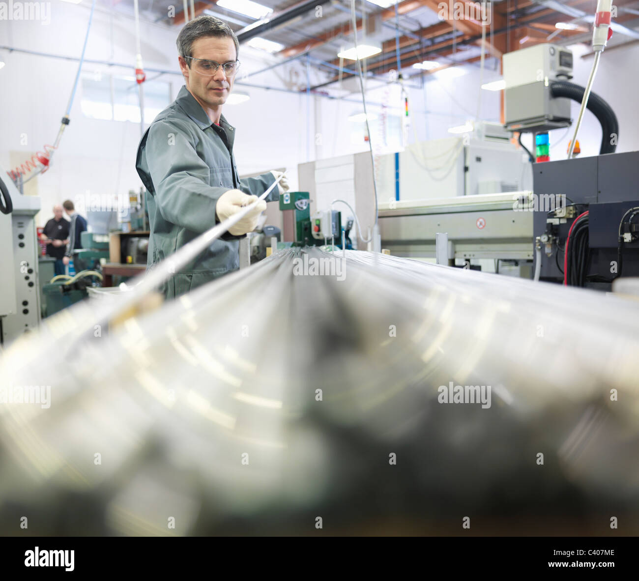 Engineer working with metal rods - Stock Image