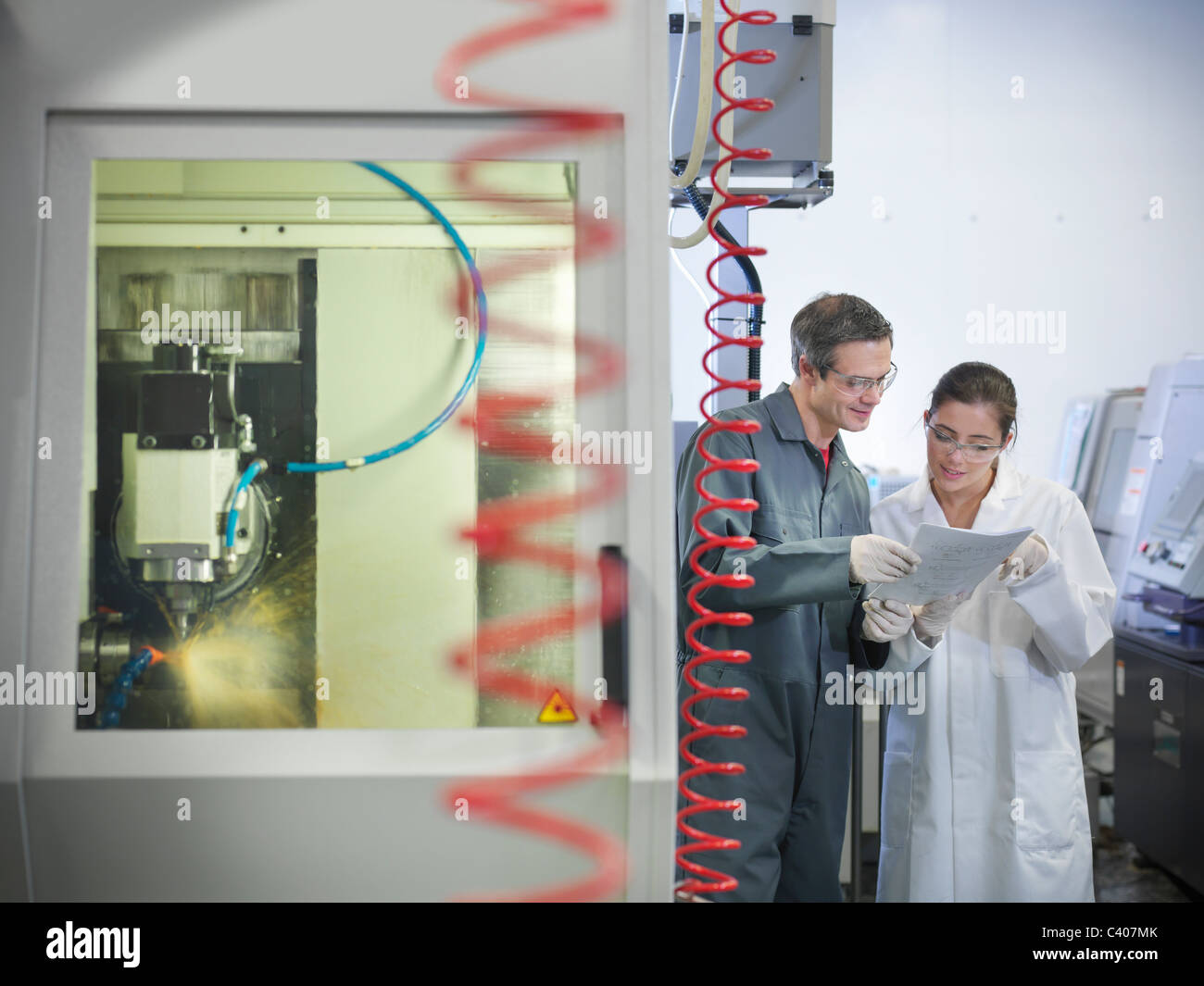 Workers next to computerised lathe - Stock Image