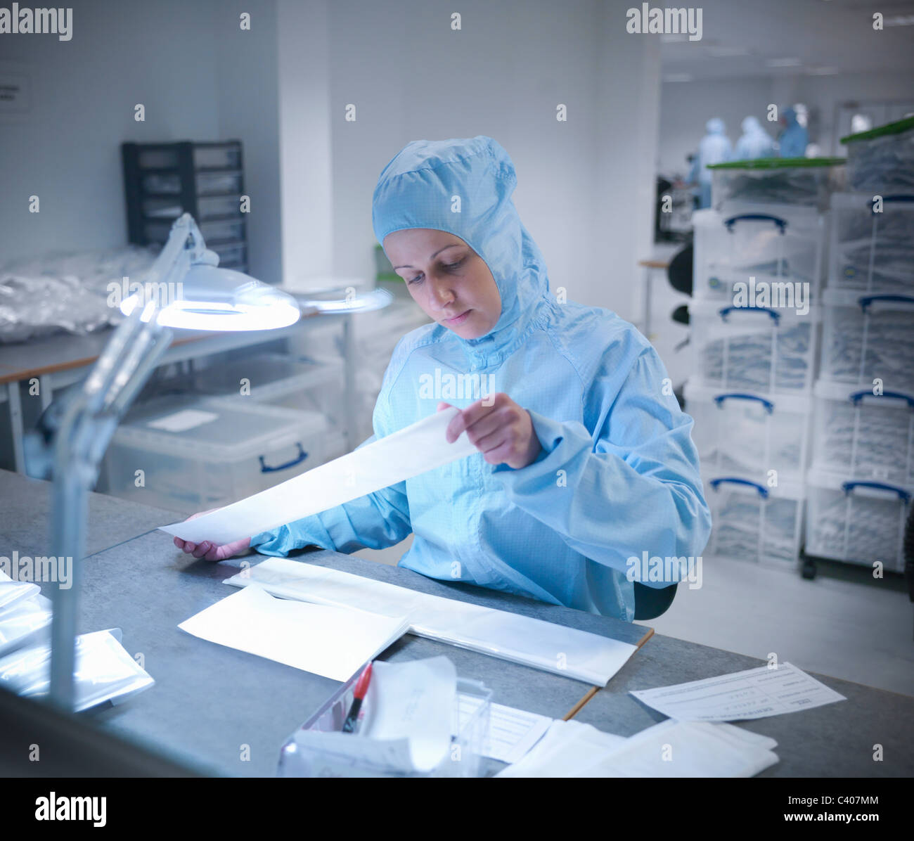 Scientist in clean room with product - Stock Image