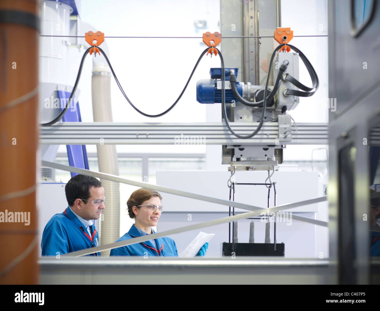 Scientists with product being processed - Stock Image