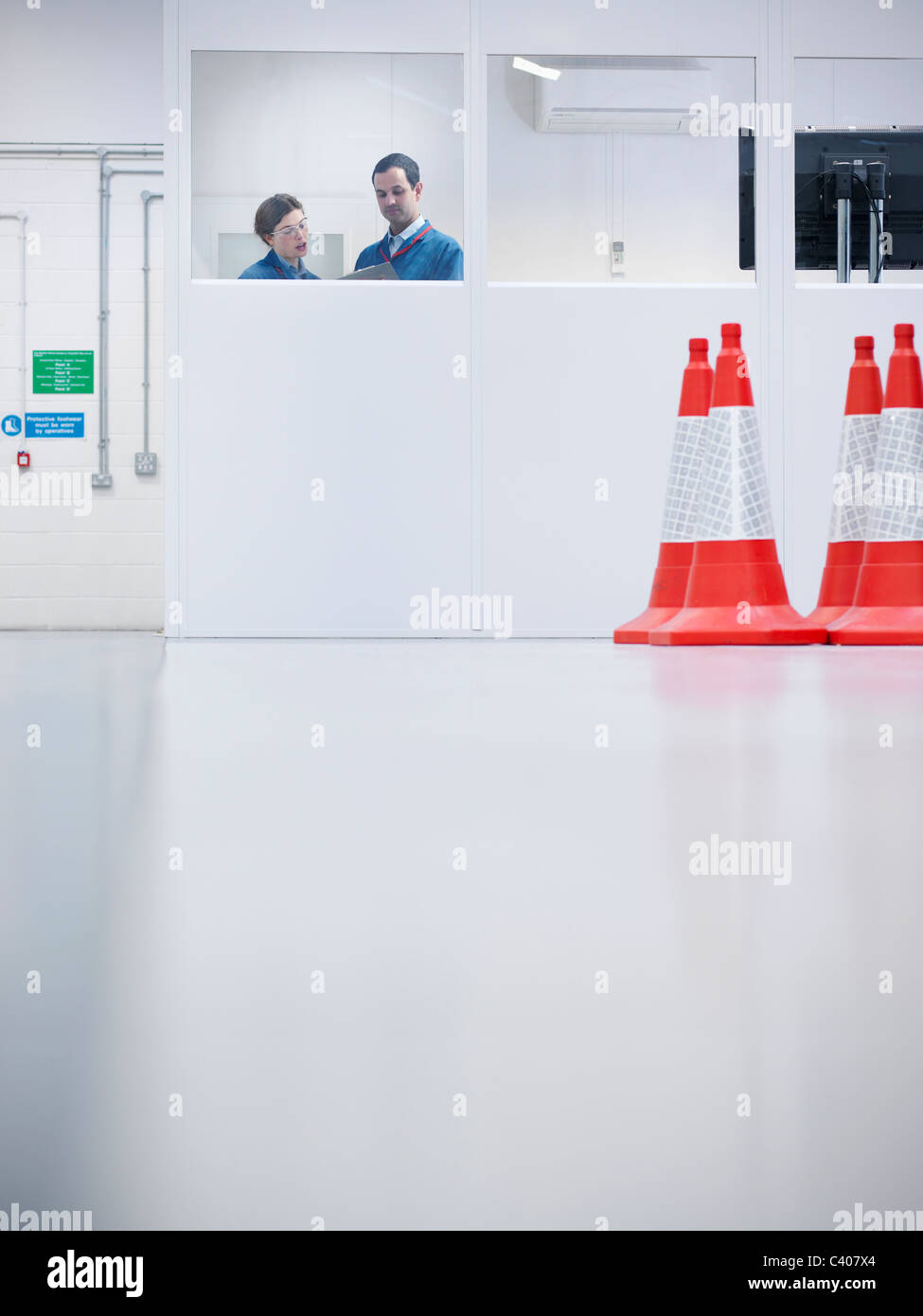 Workers in office with hazard cones - Stock Image