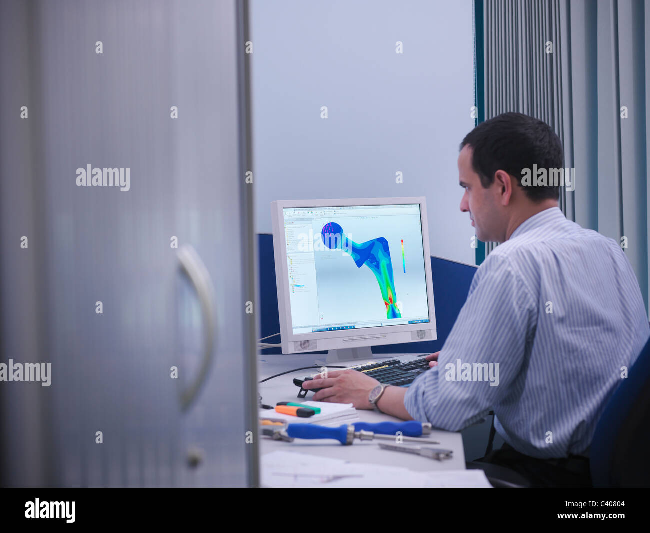 Worker with CAD drawing in office - Stock Image
