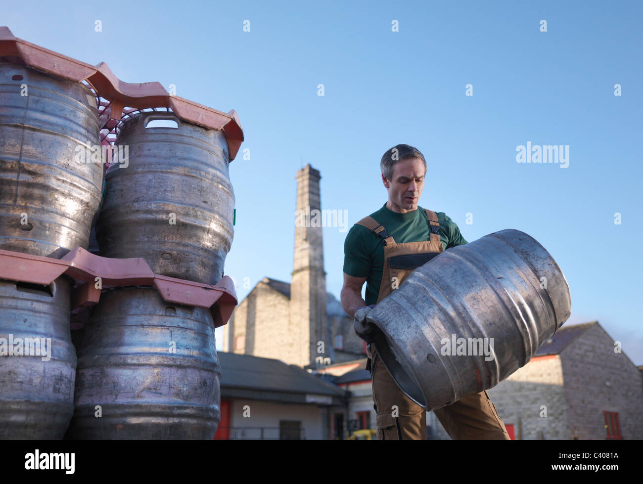 Worker carrying barrel outside brewery - Stock Image