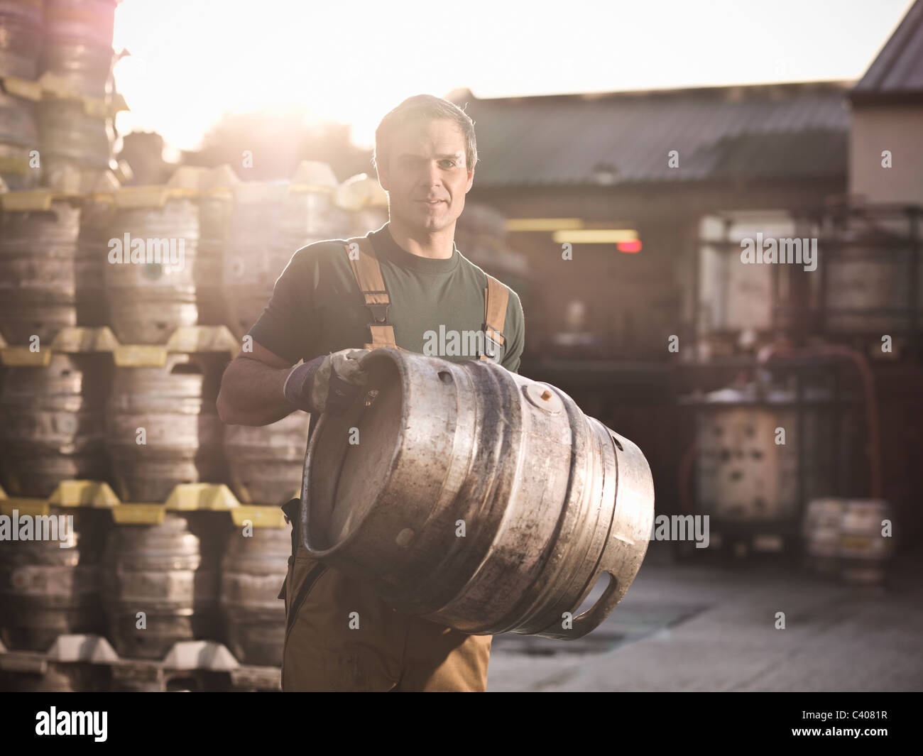 Worker with barrel outside brewery - Stock Image