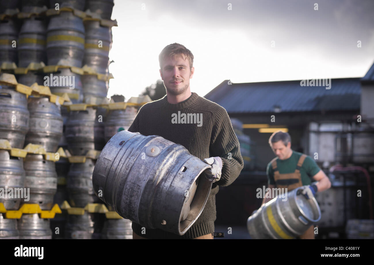 Workers with barrels outside brewery - Stock Image