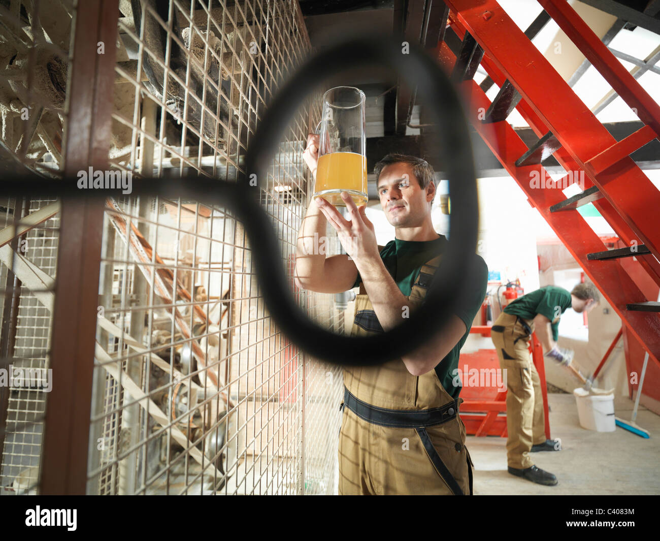 Workers in grain mill in brewery - Stock Image