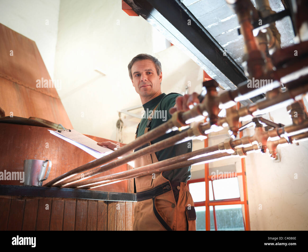 Worker turning taps at copper in brewery - Stock Image
