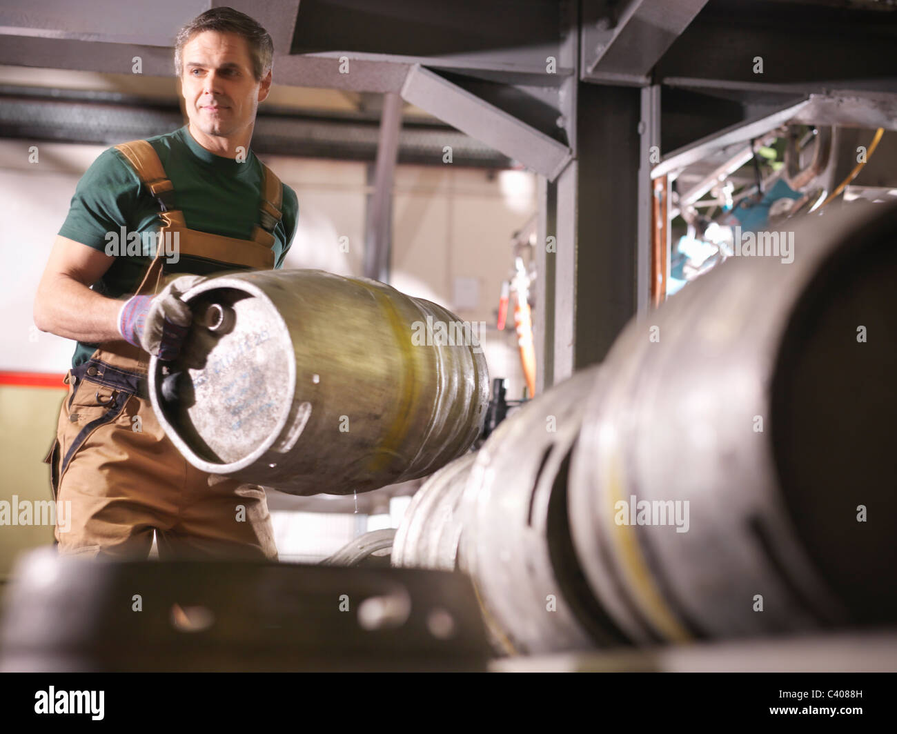 Worker lifting barrel in brewery - Stock Image