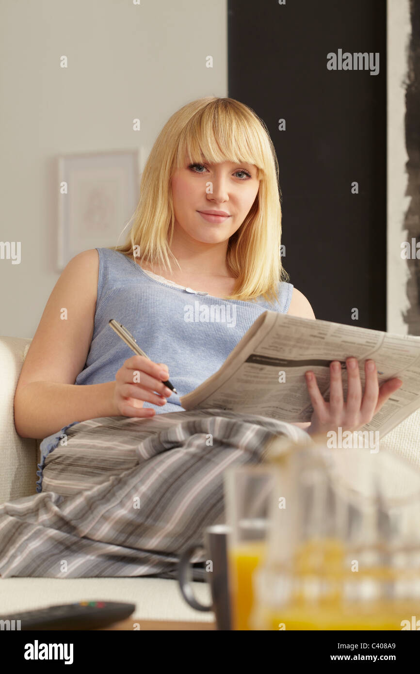 Young woman job-hunting in newspaper - Stock Image