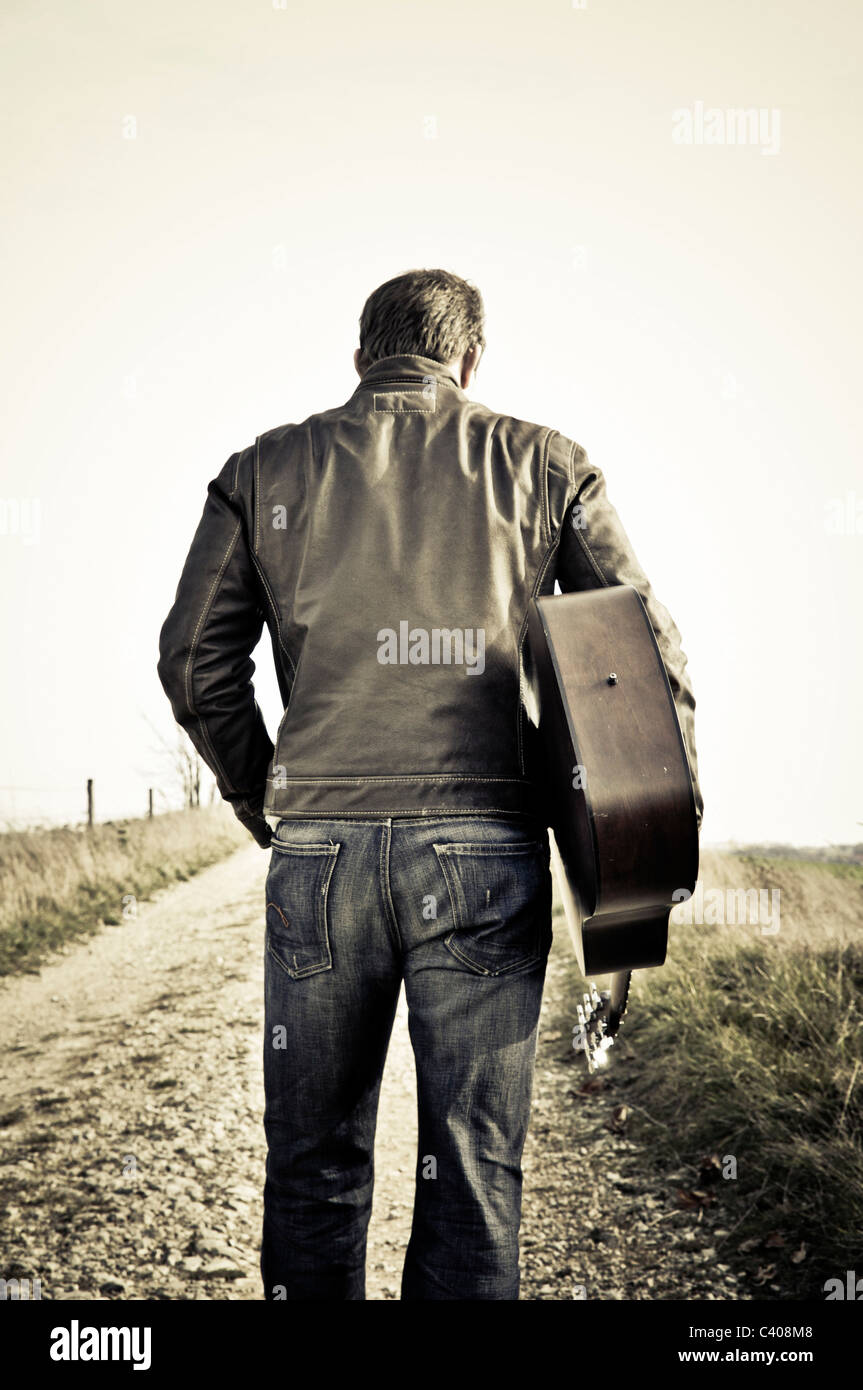 View, go outside, outdoors, outside, one, individually, along, country lane, guitar, hair, hold, behind, trousers, - Stock Image