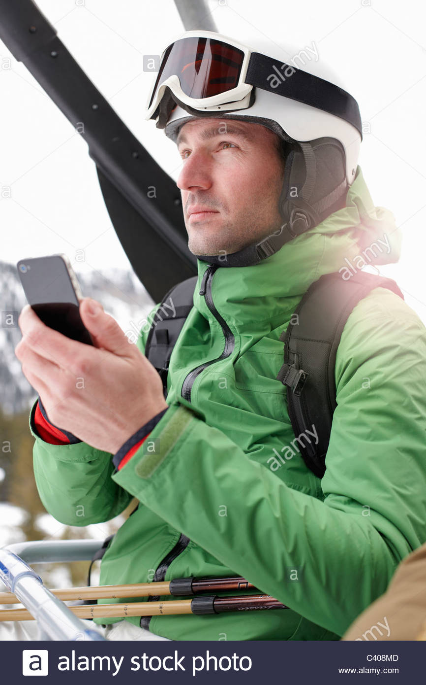Man with Smartphone in Ski lift - Stock Image