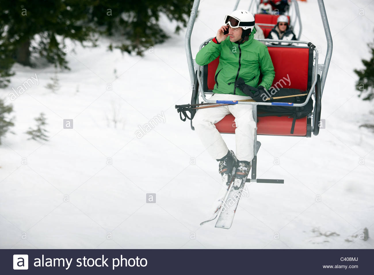 Man in Chairlift with Cellphone - Stock Image