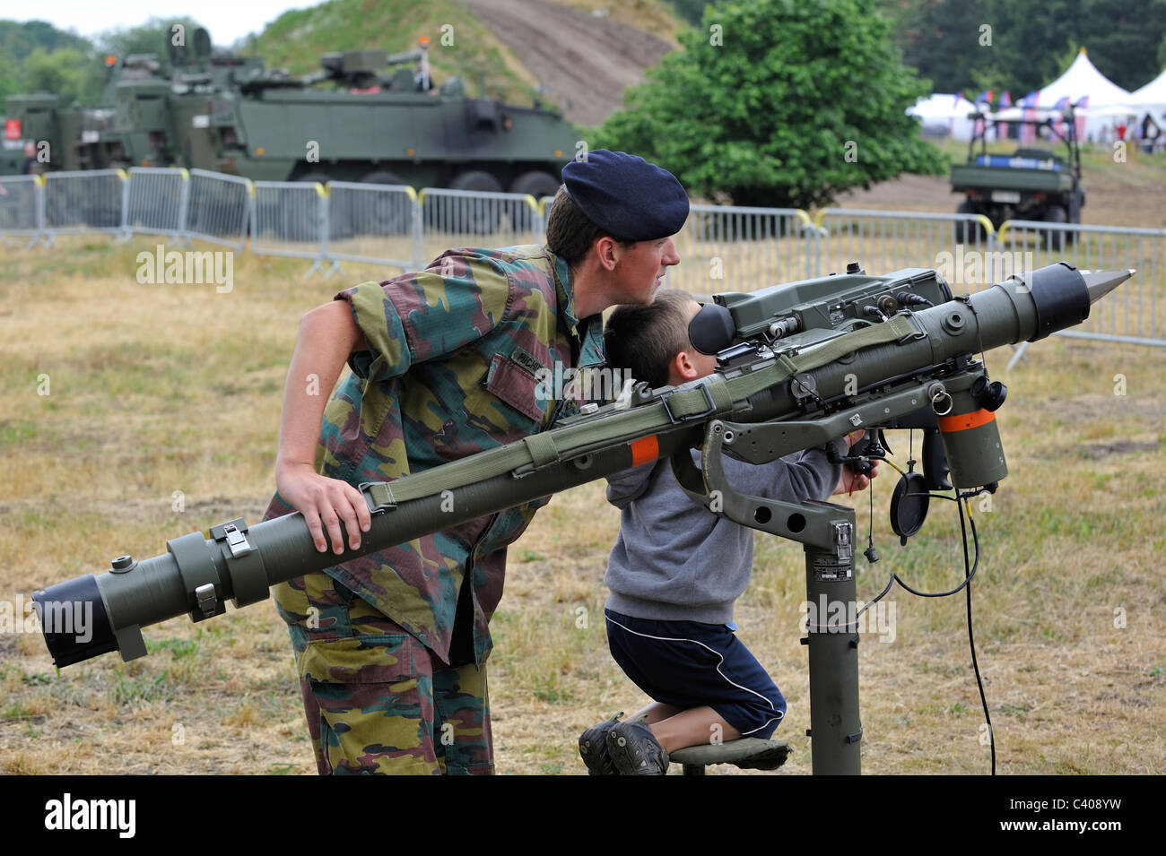 soldier showing mistral air defence missile system to child during