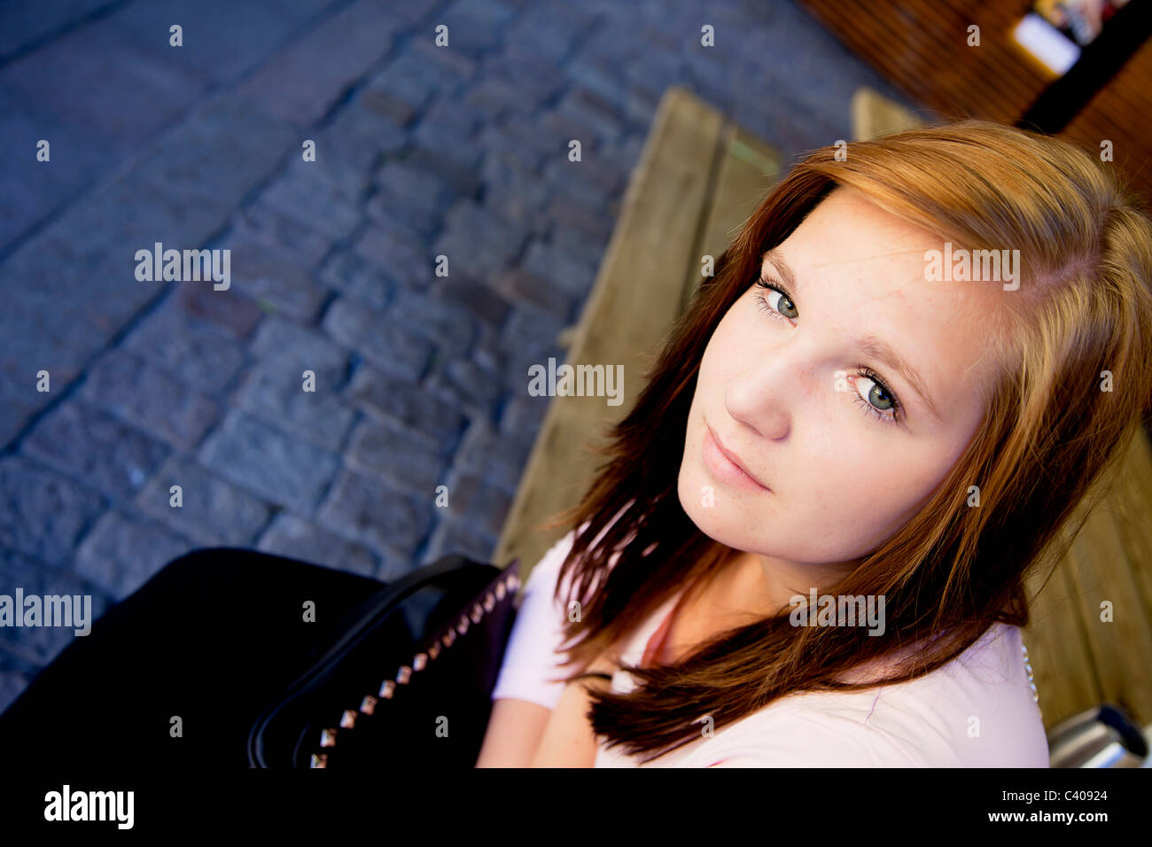 Teenage girl sitting down looking into camera - Stock Image