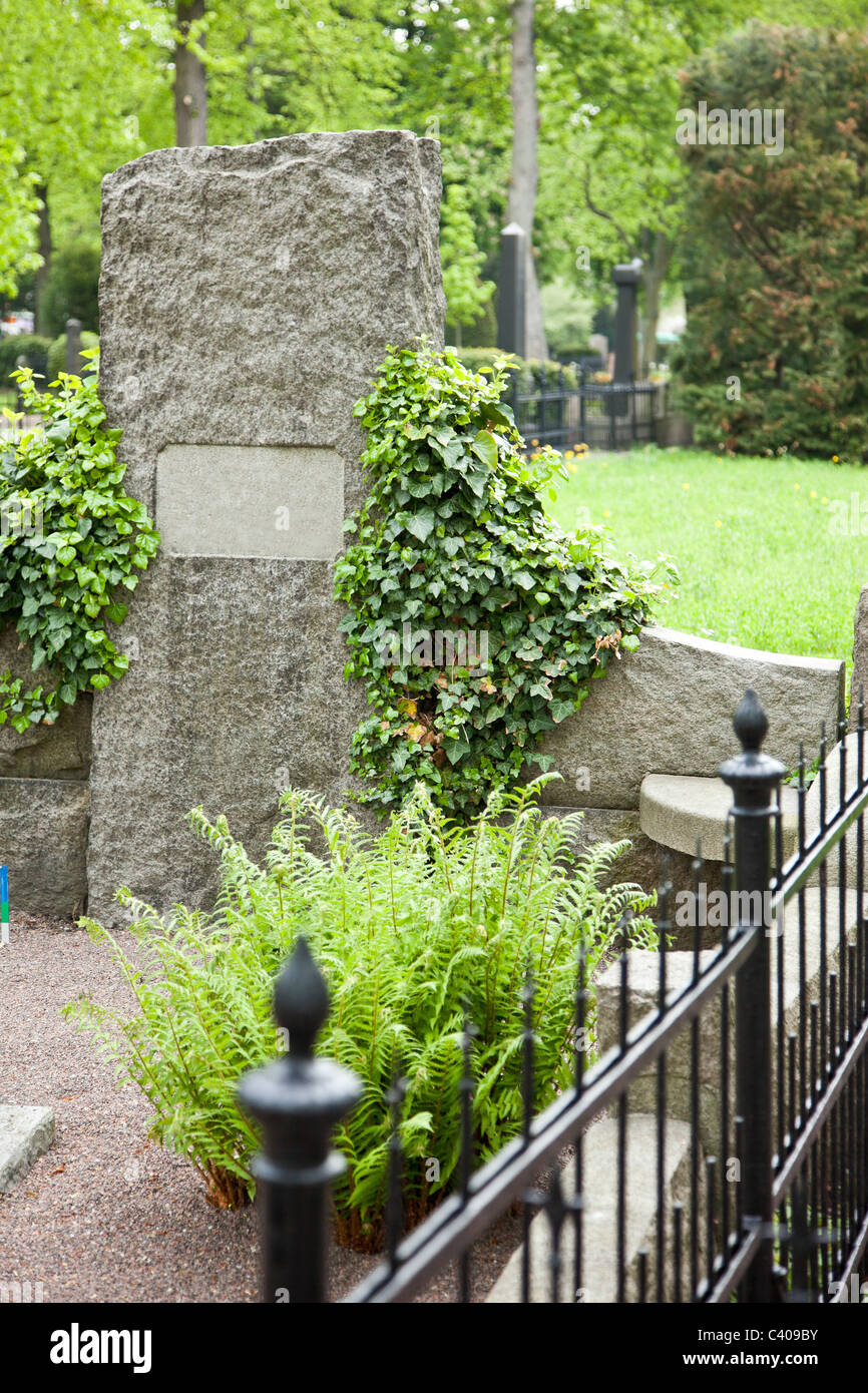 Tombstone with plants in a calm graveyard - Stock Image