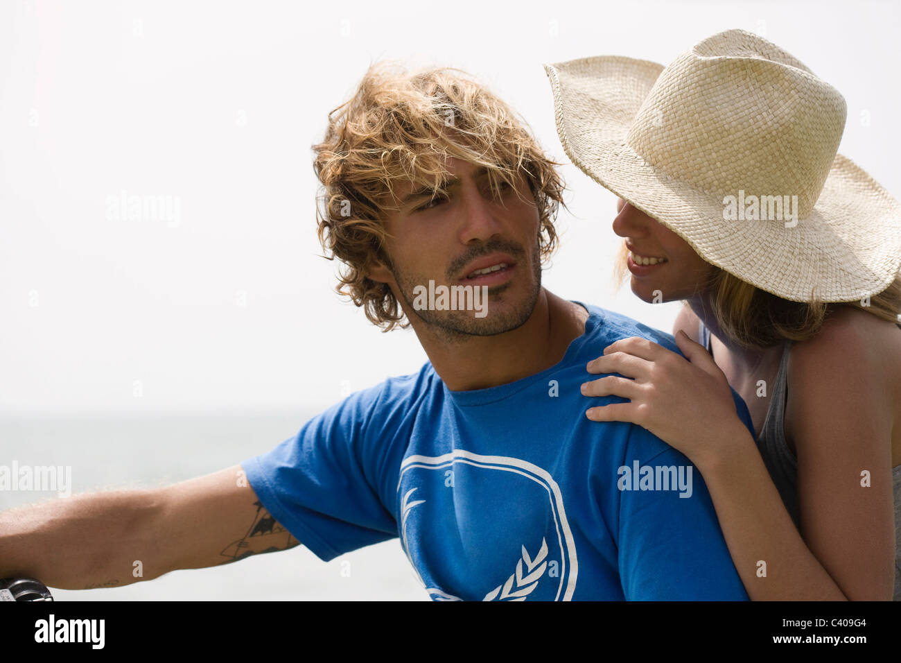 Girl with hat leaningon guys shoulder - Stock Image