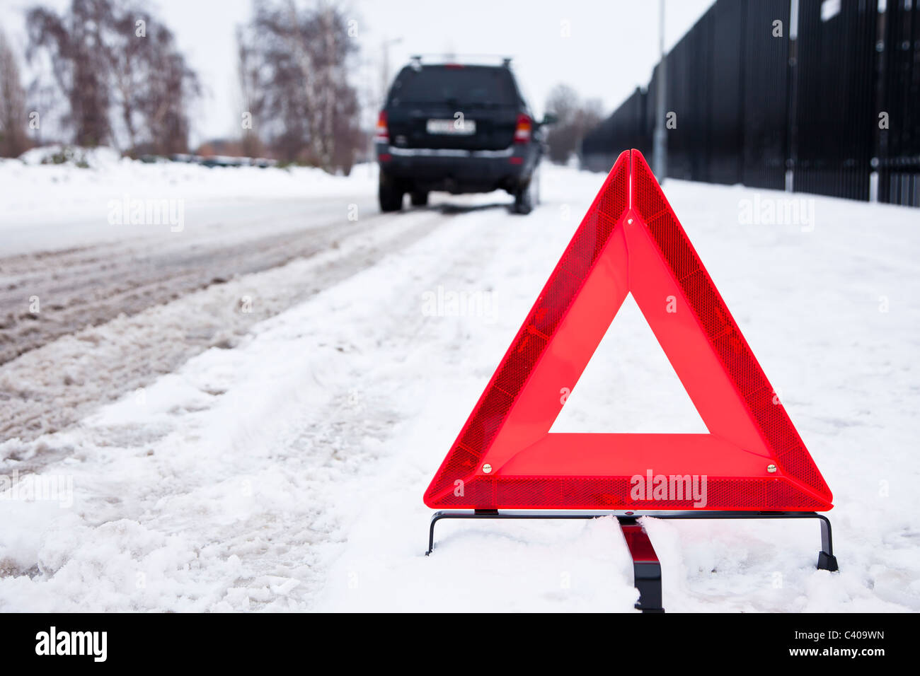 Broken car parked with a warning triangle in a snowy street - Stock Image