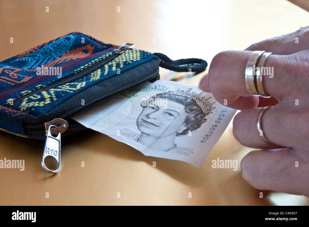 Woman's hand taking carefully a five pound note out of a purse - Stock Image
