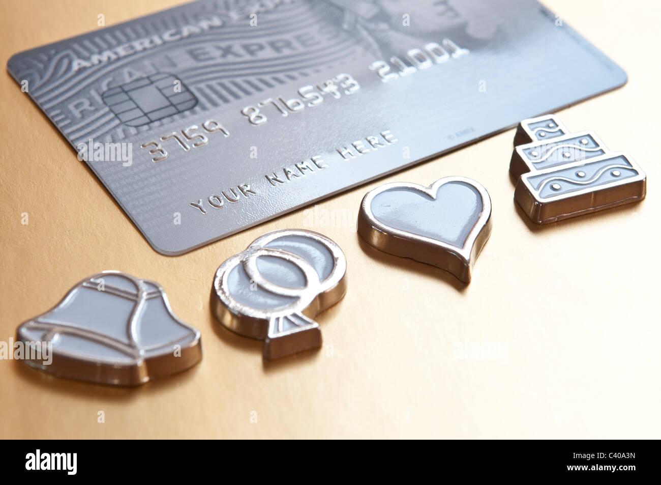Cost of  wedding. Wedding symbols, heart, bells, interlocked wedding rings, and blank credit card - Stock Image