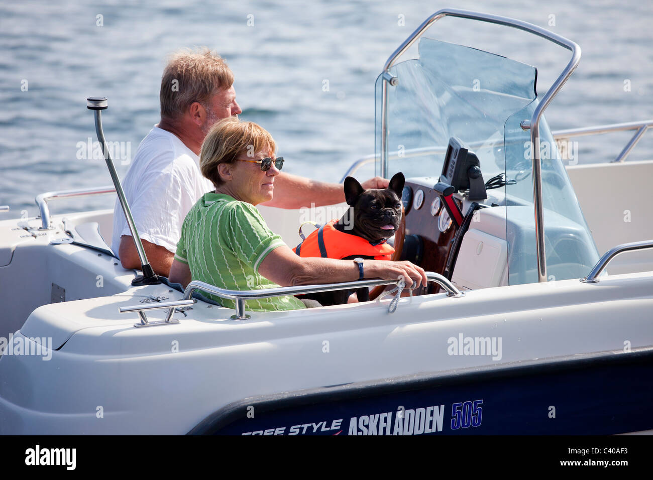 Couple in motor boat slowly cruising in the harbor. - Stock Image
