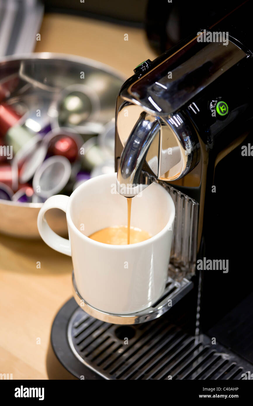 close up of Nespresso Coffee machine brewing freshly new espresso. Coffee capsules in a bowl in background - Stock Image