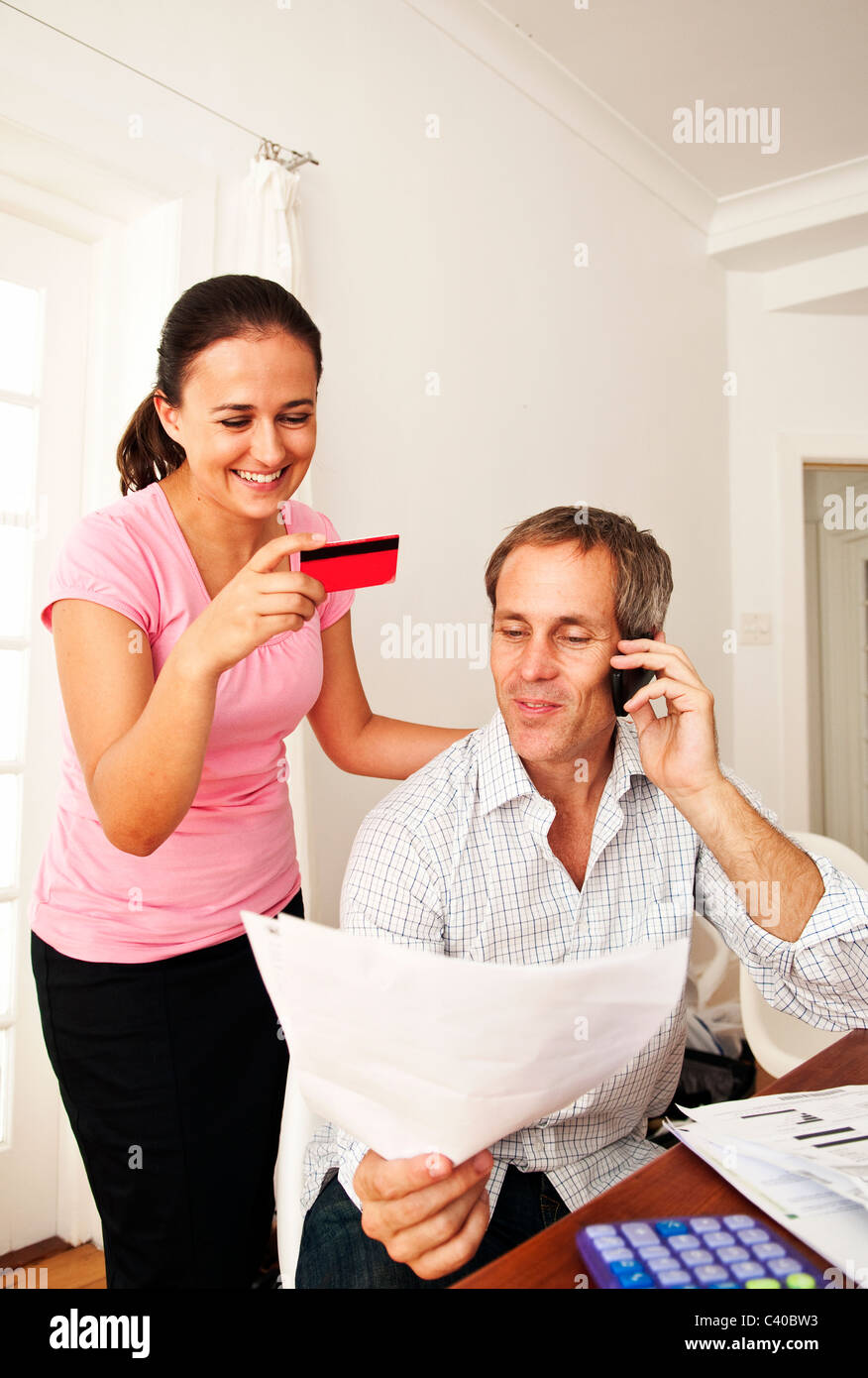 Couple pay bill with credit card - Stock Image