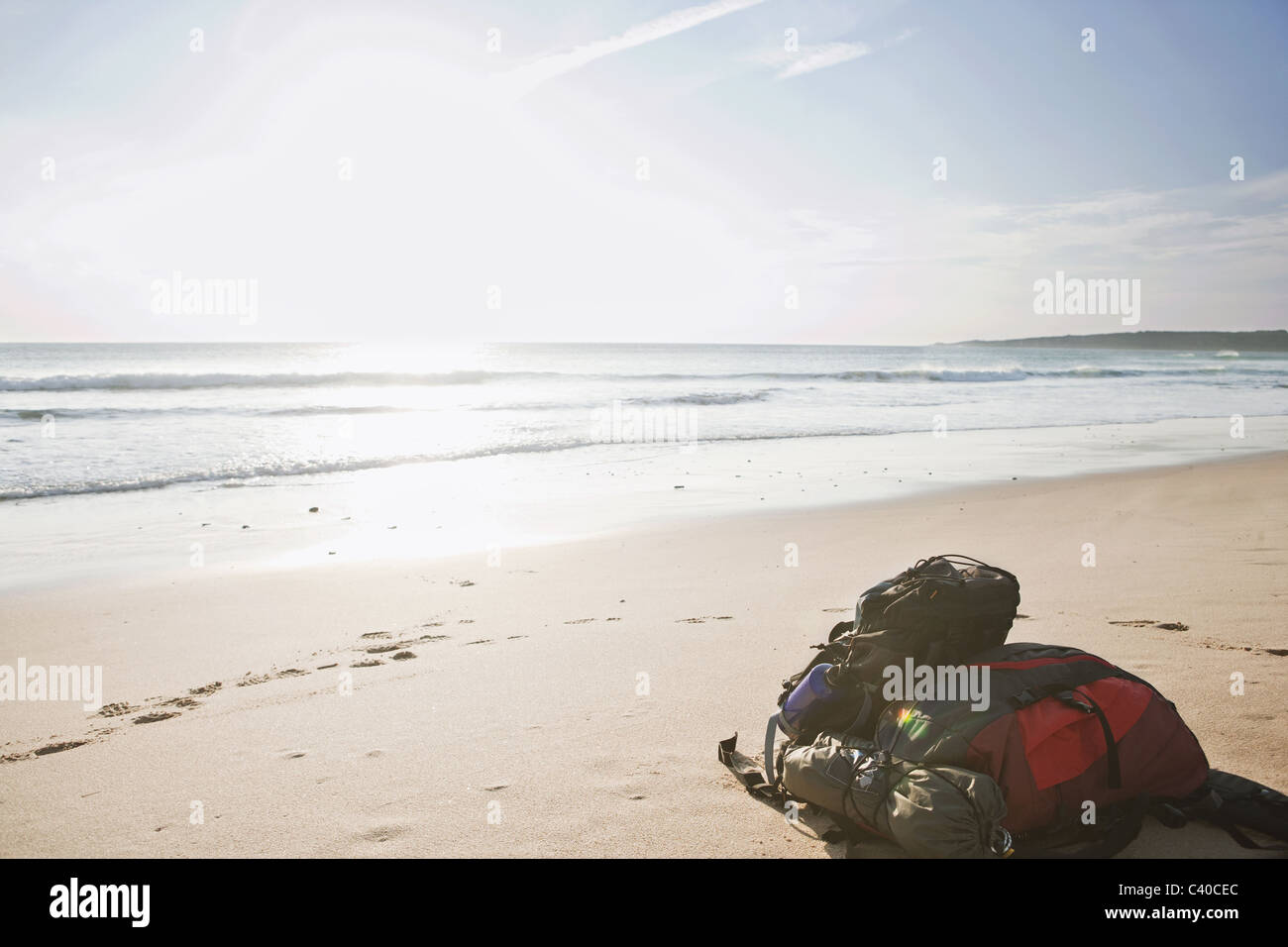 Two backpacks laid down on the beach - Stock Image